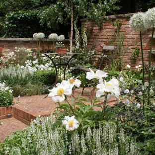 Kleiner, Halbschattiger Mediterraner Garten Im Frühling, Hinter Dem Haus  Mit Gartenmauer Und Natursteinplatten In