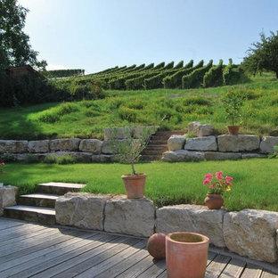 Неиссякаемый источник вдохновения для домашнего уюта: большой летний участок и сад на склоне в стиле кантри с подпорной стенкой, покрытием из каменной брусчатки и полуденной тенью