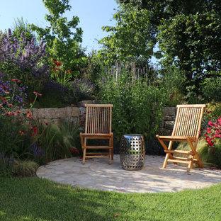 Пример оригинального дизайна: солнечный, летний участок и сад среднего размера на склоне в стиле кантри с хорошей освещенностью и покрытием из каменной брусчатки