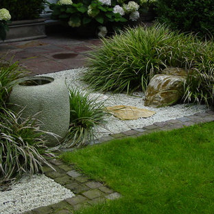 Photo of a mid-sized asian partial sun front yard stone landscaping in Bremen for summer.