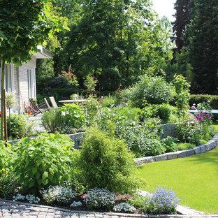 Пример оригинального дизайна: большой летний, солнечный участок и сад в стиле кантри с покрытием из каменной брусчатки, подпорной стенкой и освещенностью