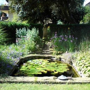 Foto på en mycket stor lantlig trädgård i delvis sol, med en damm och naturstensplattor