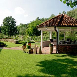 Inspiration för en mycket stor lantlig bakgård i delvis sol på sommaren, med en köksträdgård och marksten i tegel