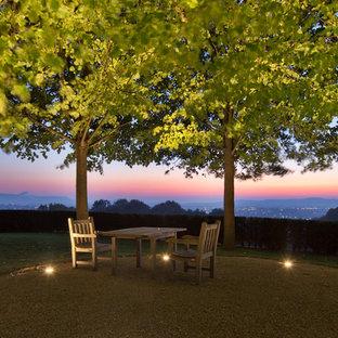 На фото: большой участок и сад на склоне в стиле кантри с полуденной тенью и покрытием из гравия с