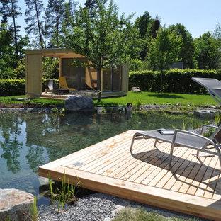 Großer Moderner Garten hinter dem Haus mit Teich und Dielen in Sonstige