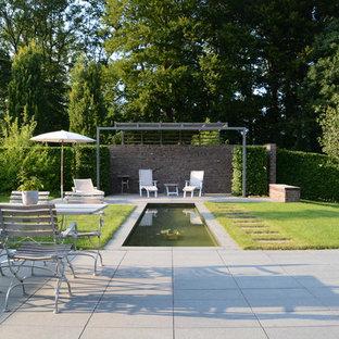 Großer, Halbschattiger Landhaus Garten neben dem Haus, im Sommer mit Wasserspiel und Betonplatten in Hamburg