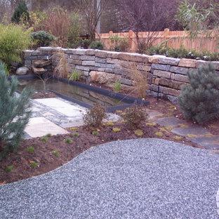 Esempio di un laghetto da giardino esposto a mezz'ombra in inverno con un pendio, una collina o una riva e ghiaia