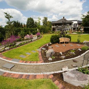Geräumiger Country Garten hinter dem Haus, im Sommer mit Gartenweg, direkter Sonneneinstrahlung und Natursteinplatten in Sonstige