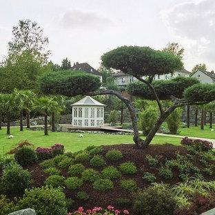 Idéer för stora orientaliska bakgårdar i full sol på sommaren, med en trädgårdsgång och naturstensplattor