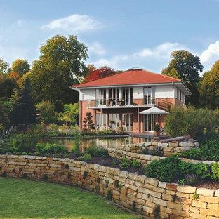 Großer, Halbschattiger Klassischer Hanggarten Im Sommer Mit Gartenmauer Und  Natursteinplatten In Berlin