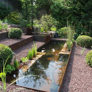 Modelo de jardín de secano, clásico, grande, en verano, en ladera, con exposición total al sol, fuente y gravilla