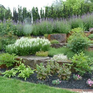 Стильный дизайн: большой солнечный, летний участок и сад на склоне в стиле кантри с подпорной стенкой, хорошей освещенностью и покрытием из каменной брусчатки - последний тренд
