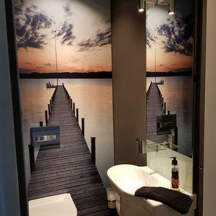 Cette photo montre un petit WC et toilettes tendance avec un placard à porte plane, des portes de placard blanches, un WC séparé, un mur marron, un sol en bois peint et un sol marron.