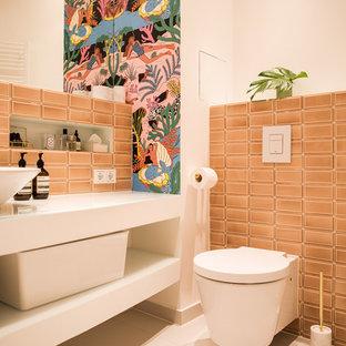 Kleine Eklektische Gästetoilette mit offenen Schränken, Wandtoilette mit Spülkasten, rosafarbenen Fliesen, Metrofliesen, Trogwaschbecken, Glaswaschbecken/Glaswaschtisch, weißer Wandfarbe, Keramikboden und beigem Boden in Berlin