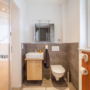 Kleine Moderne Gästetoilette mit flächenbündigen Schrankfronten, beigen Schränken, Wandtoilette mit Spülkasten, grauen Fliesen, Zementfliesen, weißer Wandfarbe, Zementfliesen, Aufsatzwaschbecken, Waschtisch aus Holz und grauem Boden in Sonstige
