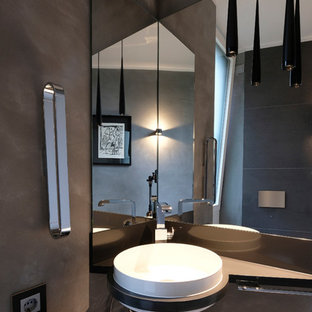 Inspiration for a small contemporary cloakroom in Dortmund with flat-panel cabinets, black cabinets, grey walls, limestone flooring, a built-in sink, black worktops and grey tiles.