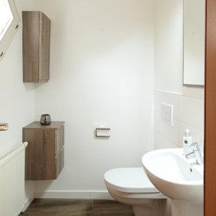Mittelgroße Gästetoilette mit dunklen Holzschränken, Wandtoilette, weißen Fliesen, Fliesen in Holzoptik und freistehendem Waschtisch in Stuttgart