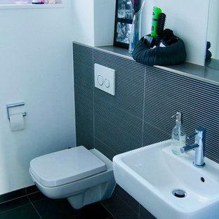 Пример оригинального дизайна: маленький туалет в современном стиле с раздельным унитазом, черной плиткой, белыми стенами, подвесной раковиной, черным полом, удлиненной плиткой и полом из цементной плитки