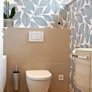 Design ideas for a mid-sized contemporary powder room in Dresden with beige tile, light wood cabinets, a wall-mount toilet, a drop-in sink, glass benchtops and multi-coloured walls.
