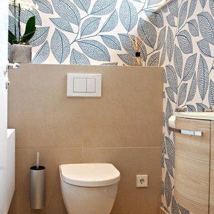 Cette image montre un WC et toilettes design de taille moyenne avec un carrelage beige, des portes de placard en bois clair, un WC suspendu, un lavabo posé, un plan de toilette en verre et un mur multicolore.