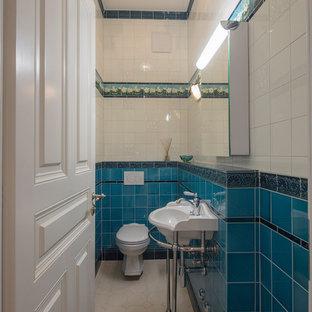 Kleine Klassische Gästetoilette mit Wandtoilette mit Spülkasten, blauen Fliesen, weißen Fliesen, Glasfliesen, Keramikboden, Wandwaschbecken, Mineralwerkstoff-Waschtisch und weißem Boden in München