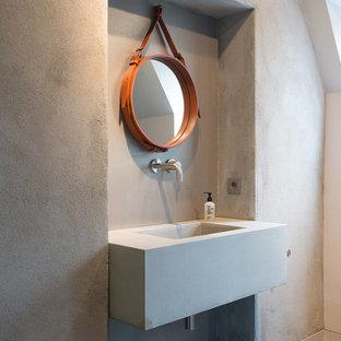 Imagen de aseo urbano con paredes grises, lavabo suspendido y encimera de cemento