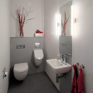 Ejemplo de aseo actual, pequeño, con urinario, baldosas y/o azulejos grises, paredes grises y lavabo suspendido