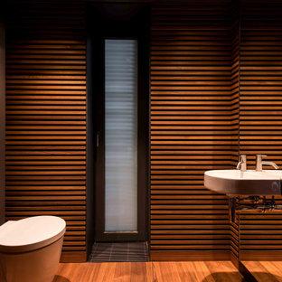 Réalisation d'un WC et toilettes design en bois de taille moyenne avec un WC suspendu, un mur marron, un lavabo suspendu et un sol marron.