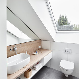 This is an example of a contemporary powder room in Dusseldorf with open cabinets, white cabinets, a wall-mount toilet, white tile, ceramic tile, white walls, a vessel sink, wood benchtops, grey floor and brown benchtops.