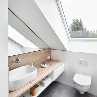 Foto di un bagno di servizio design con nessun'anta, ante bianche, WC sospeso, piastrelle bianche, piastrelle in ceramica, pareti bianche, lavabo a bacinella, top in legno, pavimento grigio e top marrone