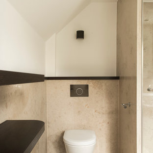 Design ideas for a small contemporary cloakroom in Dusseldorf with limestone flooring and beige floors.