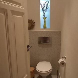Идея дизайна: маленький туалет в современном стиле с раздельным унитазом, белыми стенами, полом из галечной плитки и разноцветным полом