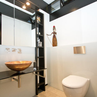 Cette photo montre un petit WC et toilettes asiatique avec des portes de placard noires, un WC suspendu, un carrelage blanc, des plaques de verre, un mur blanc, une vasque et un sol beige.