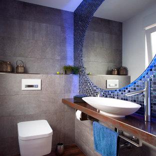 Kleine Moderne Gästetoilette mit Mosaikfliesen, dunklem Holzboden, Aufsatzwaschbecken, Kupfer-Waschbecken/Waschtisch, braunem Boden, brauner Waschtischplatte, Wandtoilette und grauen Fliesen