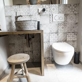 Imagen de aseo urbano, pequeño, con baldosas y/o azulejos grises, baldosas y/o azulejos de cemento, paredes beige, suelo de cemento, lavabo sobreencimera, suelo gris y encimeras negras