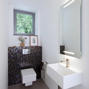 Mittelgroße Moderne Gästetoilette mit Wandwaschbecken, farbigen Fliesen, Mosaikfliesen, weißer Wandfarbe und Wandtoilette in Essen