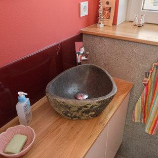 Inspiration pour un petit WC et toilettes design avec des portes de placard marrons, un WC suspendu, un carrelage rouge, un carrelage en pâte de verre, un mur rouge, un sol en vinyl, une vasque, un plan de toilette en bois, un sol gris, un plan de toilette marron et meuble-lavabo encastré.