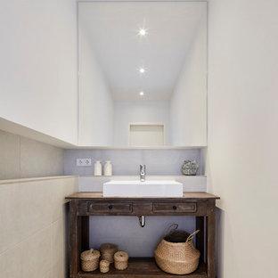 Kleine Urige Gästetoilette mit Schrankfronten mit vertiefter Füllung, dunklen Holzschränken, beigefarbenen Fliesen, Zementfliesen, weißer Wandfarbe, Keramikboden, Aufsatzwaschbecken, Waschtisch aus Holz, beigem Boden und brauner Waschtischplatte in Köln