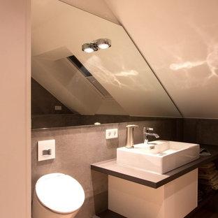 Идея дизайна: туалет среднего размера в стиле кантри с биде, серой плиткой, плиткой из сланца, белыми стенами, светлым паркетным полом, настольной раковиной, столешницей из искусственного камня, коричневым полом и серой столешницей