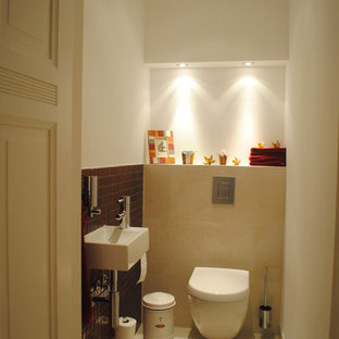 На фото: туалет в современном стиле с инсталляцией, красной плиткой, плиткой мозаикой, белыми стенами, полом из керамической плитки, подвесной раковиной и бежевым полом с