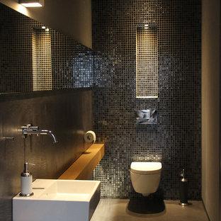 Ejemplo de aseo moderno, pequeño, con sanitario de dos piezas, baldosas y/o azulejos negros, baldosas y/o azulejos en mosaico, paredes negras, suelo de cemento, lavabo suspendido, encimera de madera, suelo gris y encimeras marrones