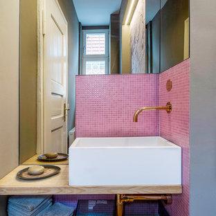 На фото: маленький туалет в современном стиле с открытыми фасадами, розовой плиткой, плиткой мозаикой, розовыми стенами, паркетным полом среднего тона, настольной раковиной, столешницей из дерева и бежевой столешницей