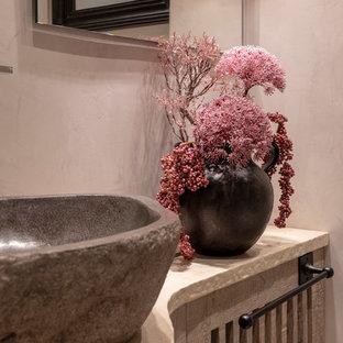 Réalisation d'un grand WC et toilettes champêtre avec un placard avec porte à panneau surélevé, des portes de placard marrons, un WC suspendu, un mur gris, une vasque, un plan de toilette en calcaire, un plan de toilette beige, un sol en calcaire et un sol beige.