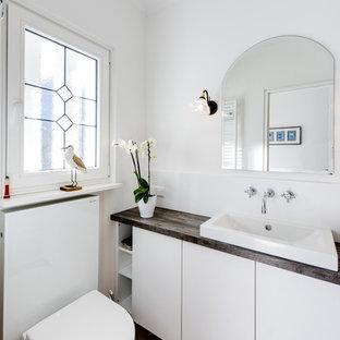 Cette image montre un petit WC et toilettes design avec un placard à porte plane, des portes de placard blanches, un WC suspendu, un carrelage blanc, des carreaux de miroir, un mur blanc, un sol en carrelage de céramique, une vasque, un sol beige, un plan de toilette en bois et un plan de toilette marron.