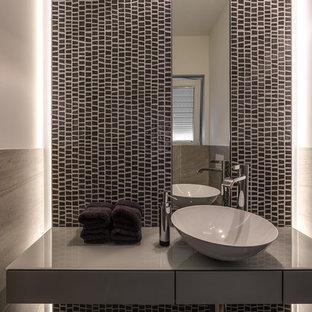Ejemplo de aseo contemporáneo, pequeño, con armarios con paneles lisos, puertas de armario grises, baldosas y/o azulejos grises, baldosas y/o azulejos en mosaico, paredes blancas, lavabo sobreencimera y encimera de vidrio
