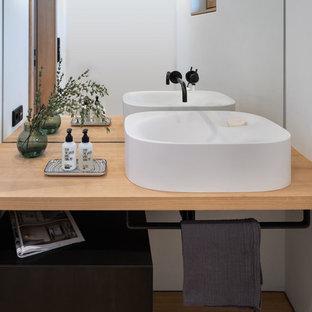 Geräumige Nordische Gästetoilette mit Spiegelfliesen, weißer Wandfarbe, hellem Holzboden, Aufsatzwaschbecken, Waschtisch aus Holz, braunem Boden und beiger Waschtischplatte in München