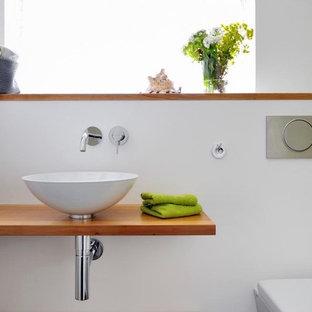На фото: маленький туалет в современном стиле с белыми стенами, открытыми фасадами, коричневыми фасадами, инсталляцией, белой плиткой, стеклянной плиткой, полом из керамогранита, настольной раковиной, мраморной столешницей и белым полом с
