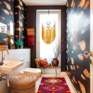 На фото: туалет среднего размера в стиле фьюжн с инсталляцией, черными стенами, полом из известняка, подвесной раковиной, столешницей из искусственного камня, бежевым полом и белой плиткой с