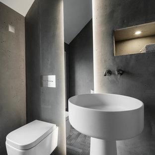 Пример оригинального дизайна: маленький туалет в стиле модернизм с инсталляцией, серыми стенами, бетонным полом, раковиной с пьедесталом, серым полом и столешницей из искусственного камня