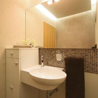 На фото: маленький туалет в современном стиле с раковиной с несколькими смесителями, коричневой плиткой, плиткой мозаикой, бежевыми стенами и полом из керамогранита